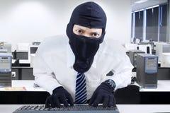 Máscara vestindo do homem de negócios que rouba a informação Imagem de Stock