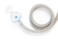 Máscara y manguera de CPAP en el fondo blanco Foto de archivo
