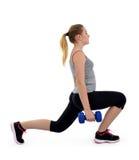 Músculos de los muslos del ejercicio de la muchacha con pesas de gimnasia Foto de archivo libre de regalías