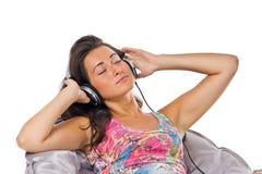 Música de escuta da mulher nova nos auscultadores Fotografia de Stock