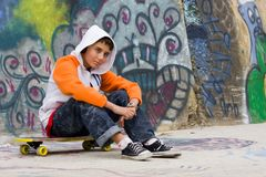 Música de escuta do adolescente perto de uma parede dos grafittis Fotografia de Stock Royalty Free