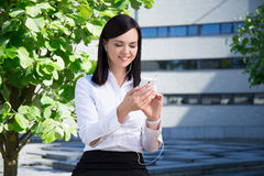 Música de escuta nova da mulher de negócio com o smartphone na paridade da cidade Foto de Stock Royalty Free