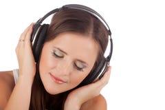 Música del disfrute de la mujer joven en auriculares Imagen de archivo libre de regalías