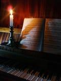 Música del piano y de hoja en la iluminación de la vela Fotografía de archivo