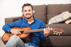 Músico de sexo masculino feliz que toca la guitarra en casa Imagen de archivo libre de regalías