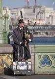Músico del Busker en el puente de Westminster, Londres, Reino Unido Foto de archivo libre de regalías