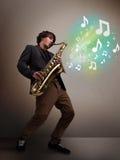 Músico joven que juega en el saxofón mientras que explodin de las notas musicales Fotografía de archivo