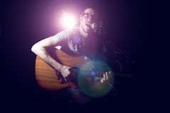 Músico que toca la guitarra acústica y que canta Fotografía de archivo libre de regalías