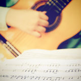 Músico que toca la guitarra clásica con los acordes musicales Imagen de archivo libre de regalías