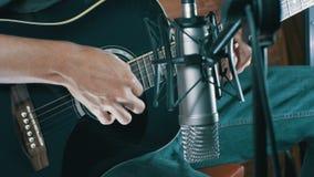 Músico Recording Acoustic Guitar no microfone no estúdio home video estoque