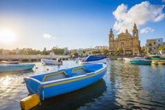 Msida, Malta - barco de pesca tradicional azul con la iglesia parroquial famosa de Msida Imagen de archivo libre de regalías