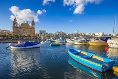 Msida, Malta - Traditional blue painted maltese fishing boat. With Msida Parish Church at background on a blue sky summer day Stock Image