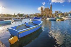 Msida, Malte - bateau de pêche traditionnel bleu avec l'église paroissiale célèbre de Msida Photos libres de droits