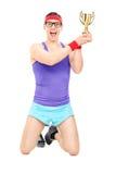 Męski atlety odświętności trofeum puszek na jego kolanach Zdjęcie Stock