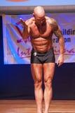 Męski bodybuilder pokazuje jego best przy mistrzostwem na scenie Obraz Stock