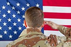 Męski żołnierz salutuje wielką usa flaga podczas gdy indoors Obrazy Stock