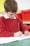 Męskiego ucznia Ćwiczy Pisać Przy stołem Zdjęcie Royalty Free