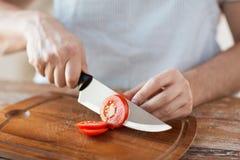 Męskiej ręki tnący pomidor z na pokładzie noża Fotografia Stock