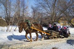 Mstera, 21,2015 Rusland-Februari: De kinderen berijden op slee met paard bij feestelijke dag van shrovetide Stock Fotografie