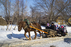 Mstera,Russia-February 21,2015: Children ride on sled with horse at festive day of the shrovetide. Small children ride on sled with horse at solar day of the Stock Photography