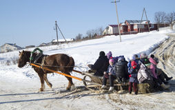Mstera,Russia-February 21,2015: Children ride on sled with horse at festive day of the shrovetide. Small children ride on sled with horse at solar day of the Royalty Free Stock Image