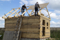 Mstera,Russia-September 14,2015: Construction of the new premises from tree. Two mans build wooden premises on background blue sky Royalty Free Stock Photos
