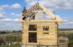 Mstera,Russia-September 14,2015: Construction of the new premises from tree. Two mans build wooden premises on background blue sky Royalty Free Stock Photo