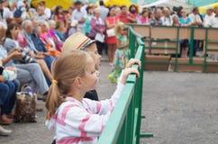 Mstyora,俄罗斯8月16,2014 :在篱芭神色conce旁边的孩子 图库摄影