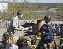 Mstyora, Rusia-mayo 9,2015: El adolescente en casquillo de ultramar sobrepone las gachas de avena de la cocina de campo Foto de archivo