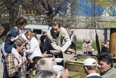 Mstyora, Rusia-mayo 9,2015: El adolescente en casquillo de ultramar sobrepone las gachas de avena de la cocina de campo Foto de archivo libre de regalías