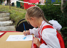 Mstyora,Russia-August 16,2014: Child draws picture on slip of paper. Mstyora,Russia-August 16,2014: Child in red peasant woman's dress and white blouse paints Stock Photography