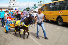 Mstyora,Russia-August 16,2014: Girl with pony carries small boy at day of the city. Mstyora,Russia-August 16,2014: Girl with pony carries on road of the small Royalty Free Stock Images