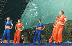 Mstyora,Russia-August 16,2014: Young girls dance on scene at day. Mstyora,Russia-August 16,2014: Group young girl in blue and orange suit dance on scene at day Stock Photo