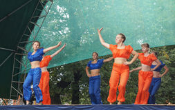 Mstyora,Russia-August 16,2014: Young girls dance on scene at day. Mstyora,Russia-August 16,2014: Group young girl in blue and orange suit dance on scene at day Royalty Free Stock Image