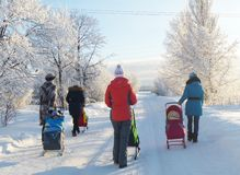Mstyora,Russia-January 24,2013: Young mas and children on walk in winter. Mstyora,Russia-January 24,2013: Young mas and small children on walk at winter solar Royalty Free Stock Photo