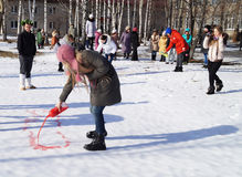 Mstyora Ryssland-Februari 28,2014: Flickan drar rött vatten på snö Royaltyfria Bilder