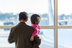 MSY, homme et enfant regardant la fenêtre l'avion Photos stock