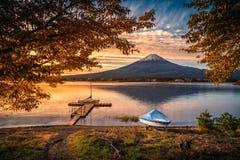 Mt 在湖Kawaguchiko有秋天叶子的和小船的富士在日出在富士河口湖町 免版税库存图片