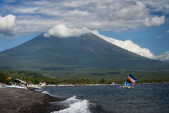 Mt. Agung, Amed, Bali. The active volcano, Mt. Agung, looms over the small fishing village of Amed on the east coast of Bali, Indonesia. Fishermen use colorful Royalty Free Stock Image