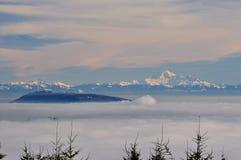 Mt-bagare och Burnaby berg som uppstår upp från ett hav av moln Royaltyfria Foton
