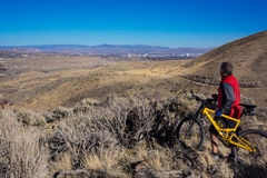 Mt Bike Over Reno. Mountain Biker stops on an over look to take in the view of Reno Nevada royalty free stock image