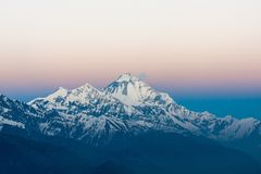 Mt. Dhaulagiri, Nepal. Beautiful snowy mountain peak in gentle morning lights. Snowy mountain peak lit by first pinkish sunrise rays. Majestic snowy mountain royalty free stock photos