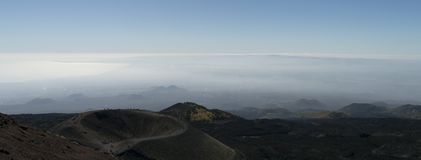 Mt Etna Panorama showing a crater and with clouds in the background royalty free stock photo