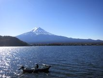 Mt. Fuji with a Boater Out on Lake in Front of Mountain. An image of Mt. Fuji in Japan with a boater out on the lake in front of Mount Fuji Stock Photo
