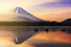 Fujisan at sunrise in Shoji lake. Mt. Fuji or Fujisan with Silhouette three fishermen on boats and mist at Shoji lake during dawn and sunrise in Yamanashi, Japan Stock Image