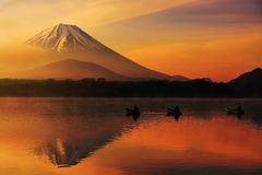 Lake shoji at sunrise with Mt. Fuji. Mt. Fuji or Fujisan with Silhouette three fishing people on boats and mist at Shoji lake with twilight sky at sunrise in Stock Images