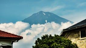 Mt.Fuji over Fujinomiya, Shizuoka, Japan. View of Mt.Fuji and clouds over Fujinomiya roofs, Shizuoka, Japan Royalty Free Stock Photo