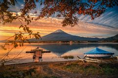 Mt. Fuji over Lake Kawaguchiko with autumn foliage and boat at sunrise in Fujikawaguchiko, Japan royalty free stock images