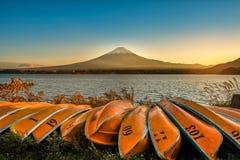Mt. Fuji over Lake Kawaguchiko with boats at sunset in Fujikawaguchiko, Japan. stock photo
