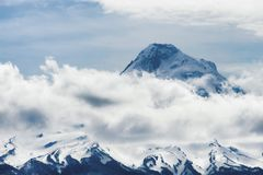 Clouds surrounds Mt. Hood in Mt. Hood National Forest. Mt. Hood enhanced with sunlight and clouds a volcano peak in the Oregon Cascade Mountain Range Stock Photo